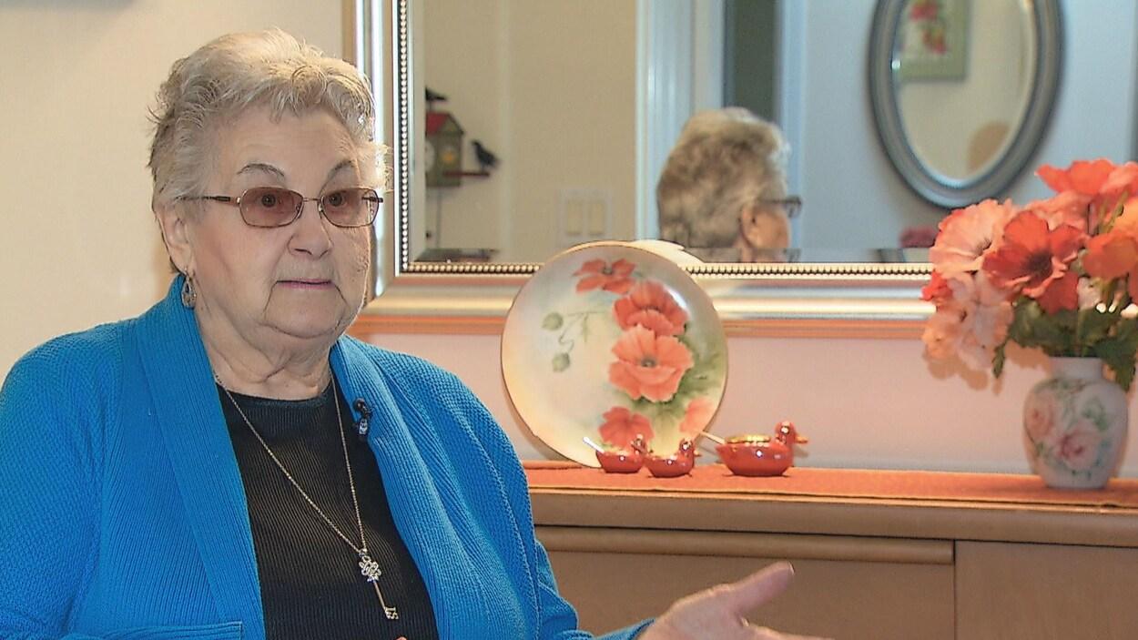 Marie Robillard, assise à une table, devant un miroir et une assiette en céramique.