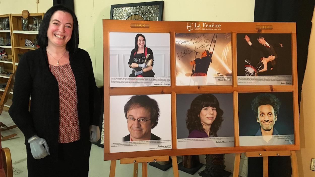 Souriante, une femme avec des mains bioniques pose avec, à sa gauche, un tableau affichant le visage de six personnes.