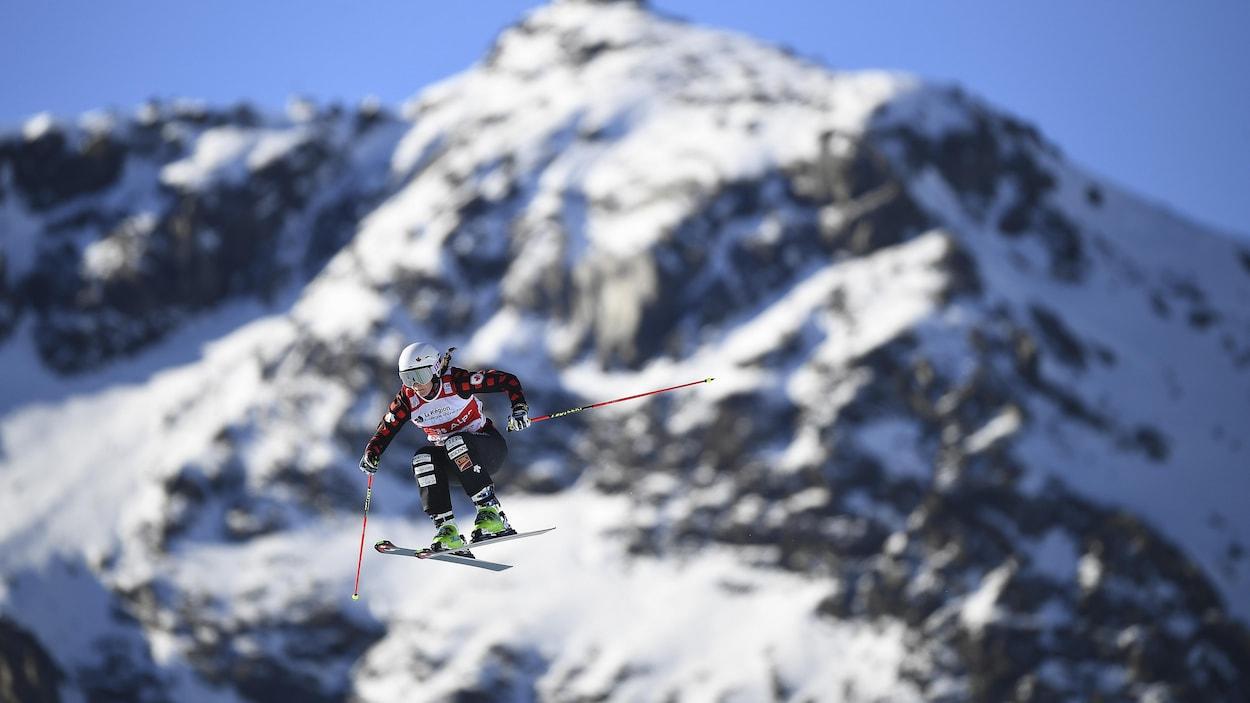 Le skieuse canadienne dans les airs pendant une épreuve de ski cross. En arrière-plan, une montagne enneigée.