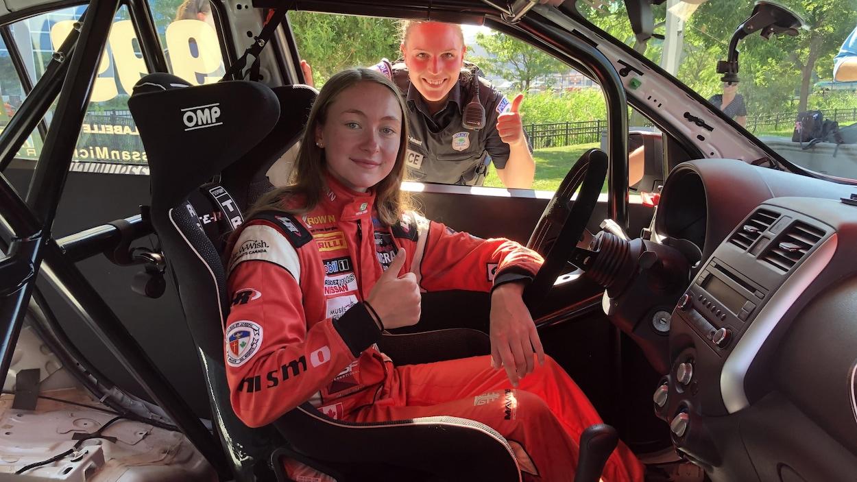 Marie-Soleil Labelle et une agente du Service de police de la Ville de Gatineau posent dans une voiture de course, avec un pouce levé.