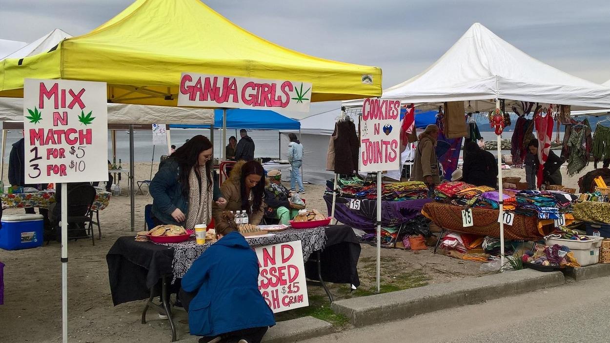 Trois femmes autour d'une table ont des biscuits à la marijuana à vendre sur la plage Sunset lors du 4/20 organisé à Vancouver en avril 2018.