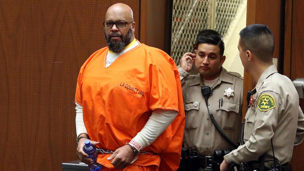 Marion «Suge» Knight, menottes aux poignets, arrive dans la salle du tribunal, regardant les objectifs des photographes. Un policier marche derrière lui.