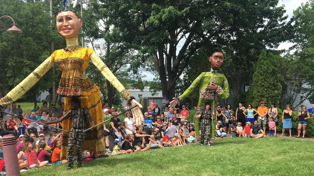 Deux marionnettes géantes devant une foule.