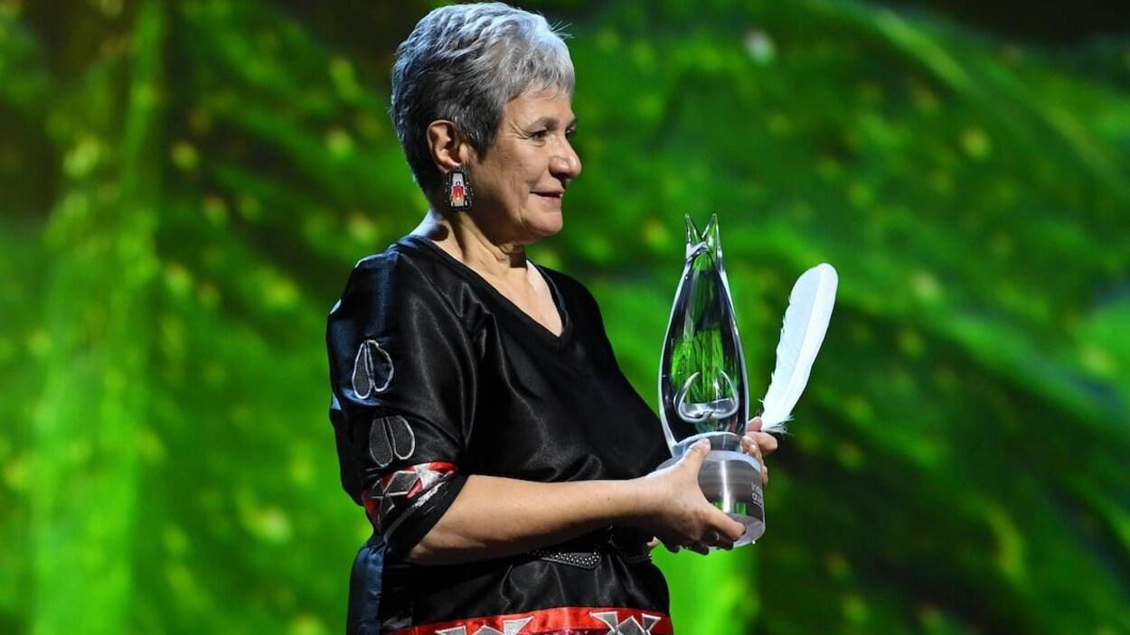 Une femme tient dans ses mains un prix qui lui a été remis, et une plume blanche.