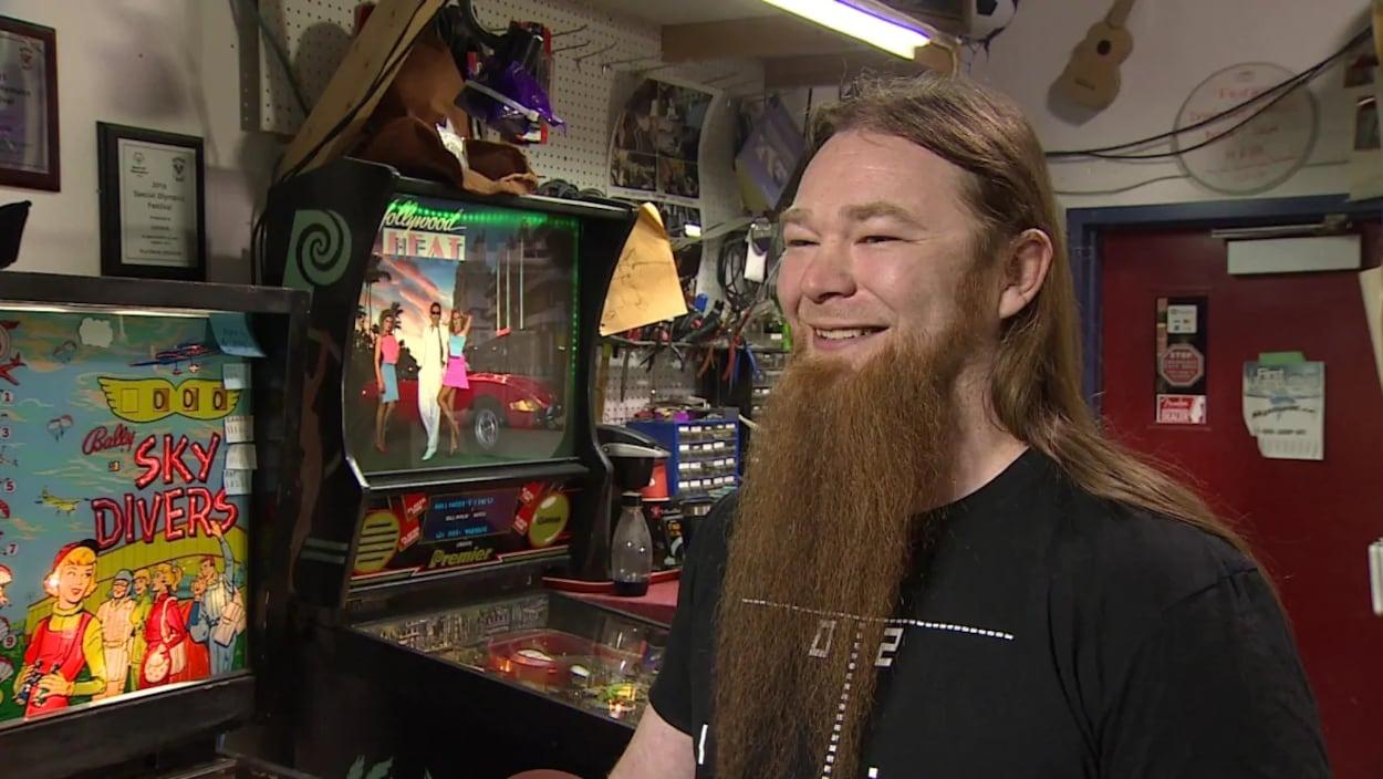 Marshall Charlebois devant des machines d'arcades.