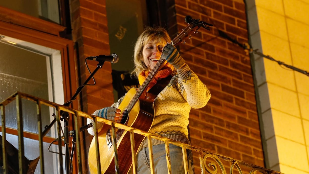 Martha Wainwright au micro avec une guitare.