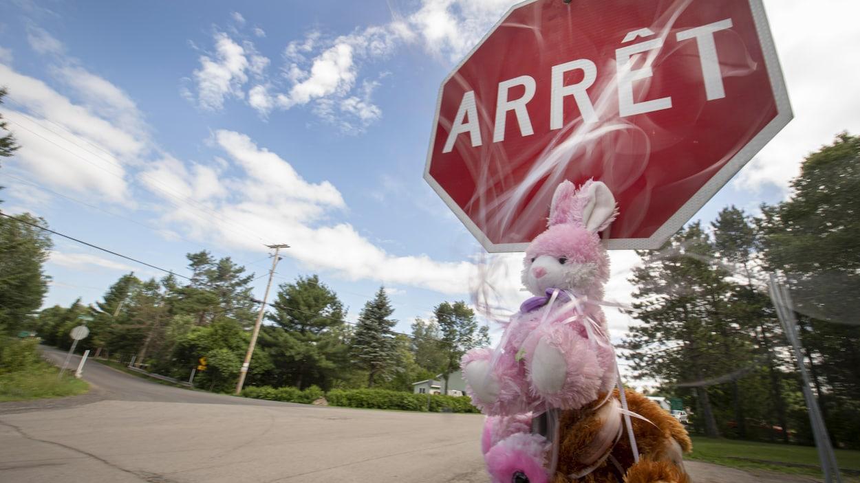 Des toutous en peluche accrochés près d'un panneau arrêt.