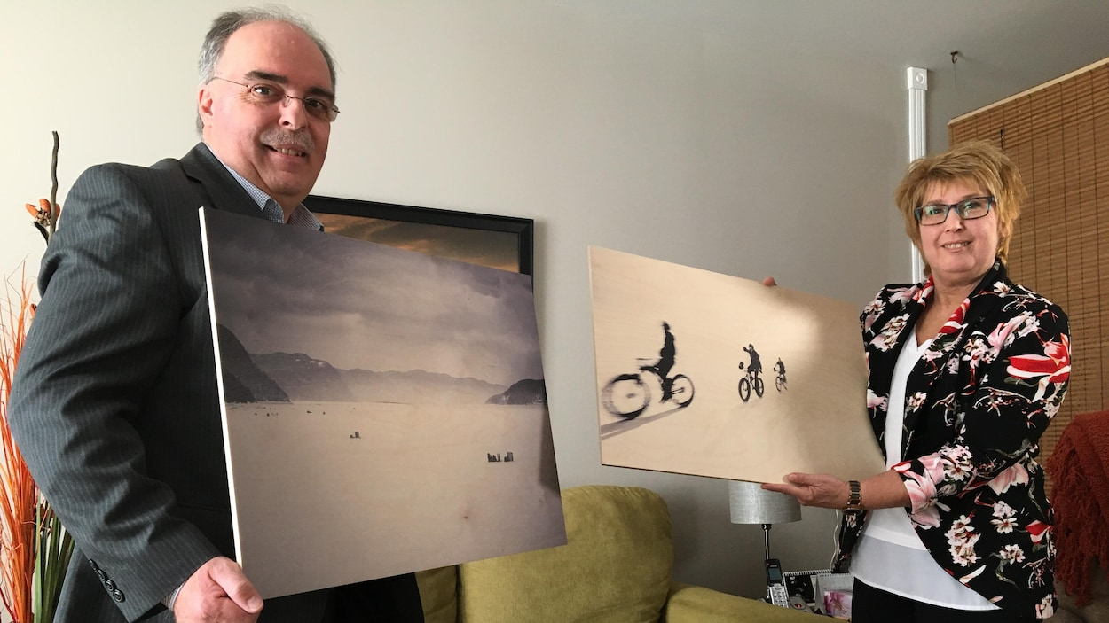 Un homme et une femme tiennent dans leur main une photo.