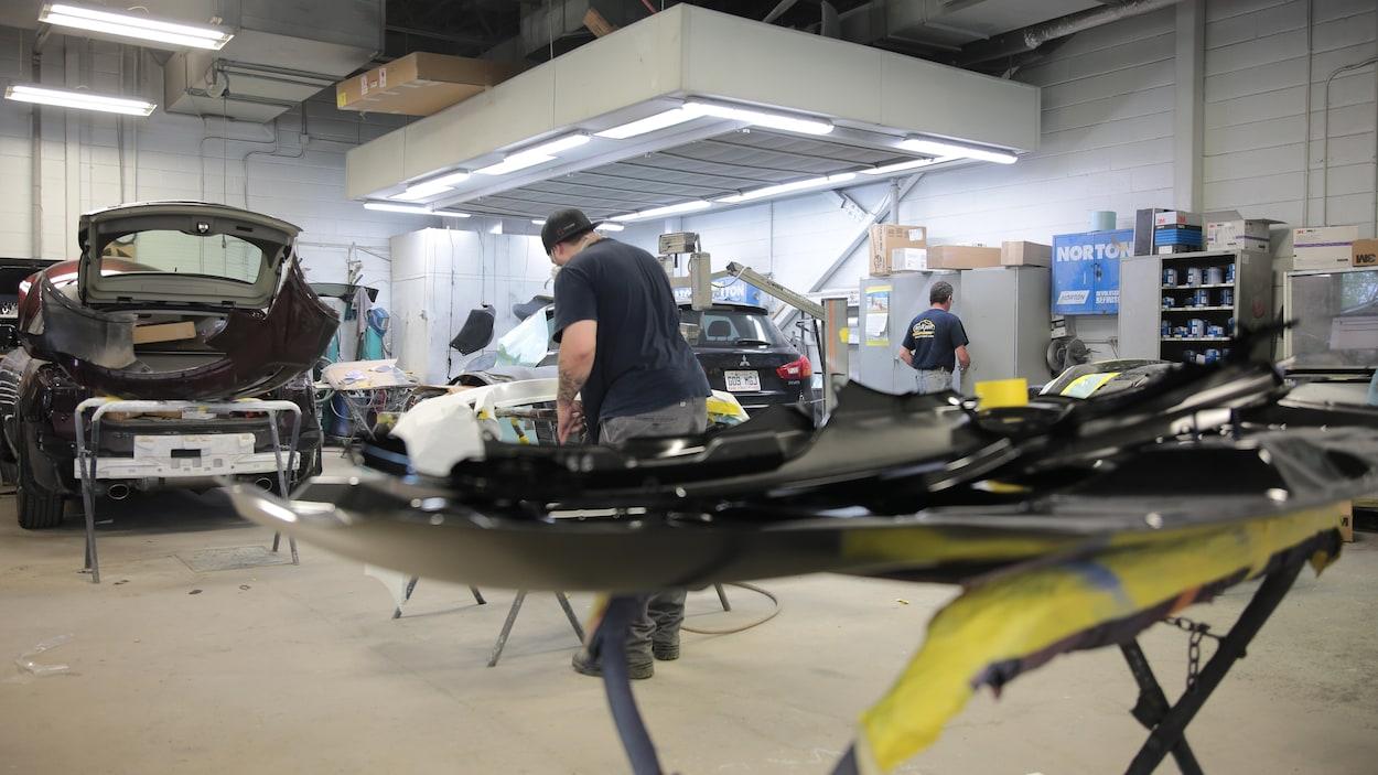 Deux hommes de dos dans un atelier de mécanique automobile.