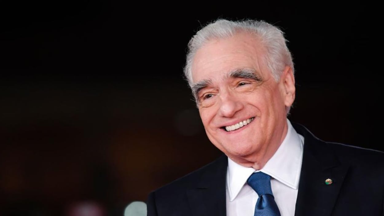 Martin Scorsese sourit et porte un complet sombre ainsi qu'une cravate bleue.