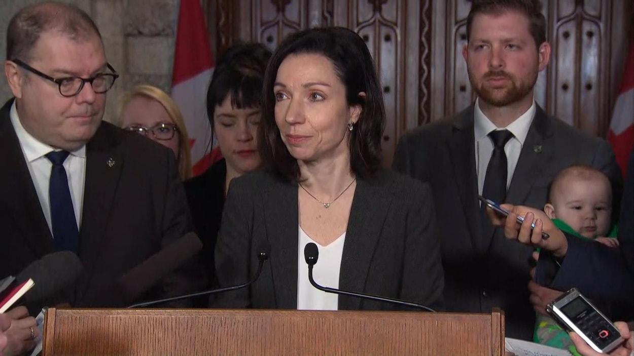 La chef du Bloc québécois, Martine Ouellet, répond aux questions des journalistes sous le regard du député Mario Beaulieu (à gauche), le 28 février 2018.