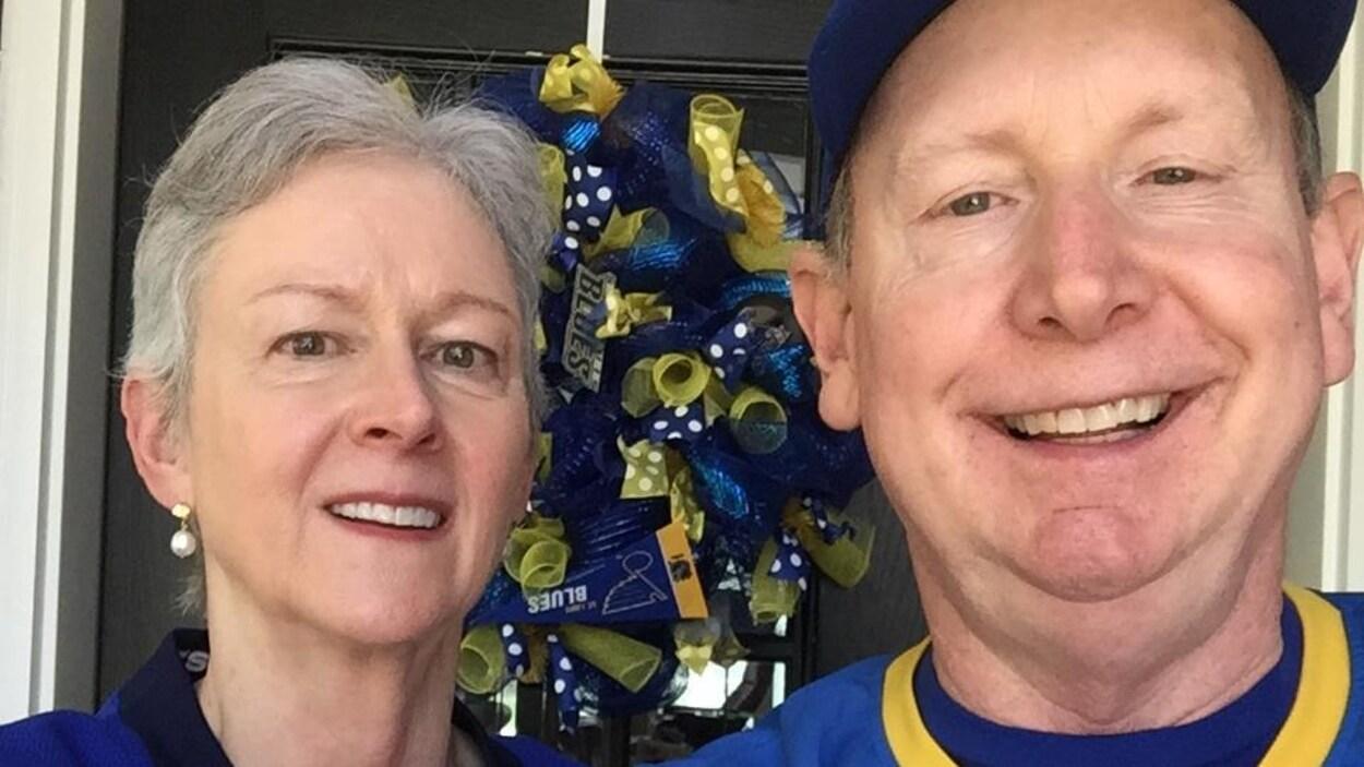 Une femme et un homme sexagénaires, vétûs de chandails de hockey, se prennent en égo-portrait.