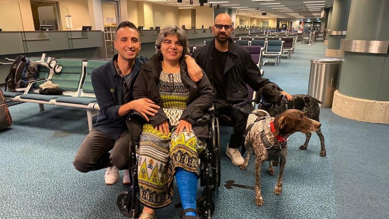 Deux hommes se tiennent aux côtés d'une femme en fauteuil roulant dans une salle d'attente d'un aéroport.