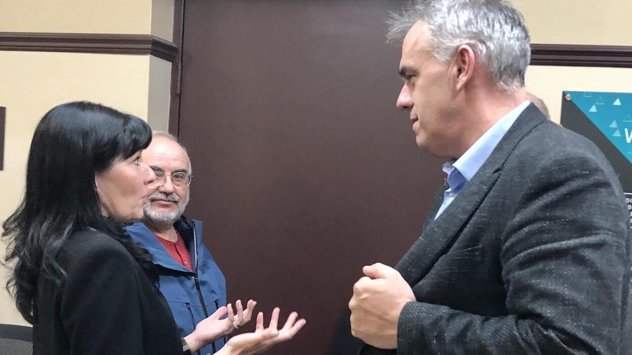 Une femme discute avec un homme qui lui fait face tandis qu'à sa gauche, un homme écoute la conversation.
