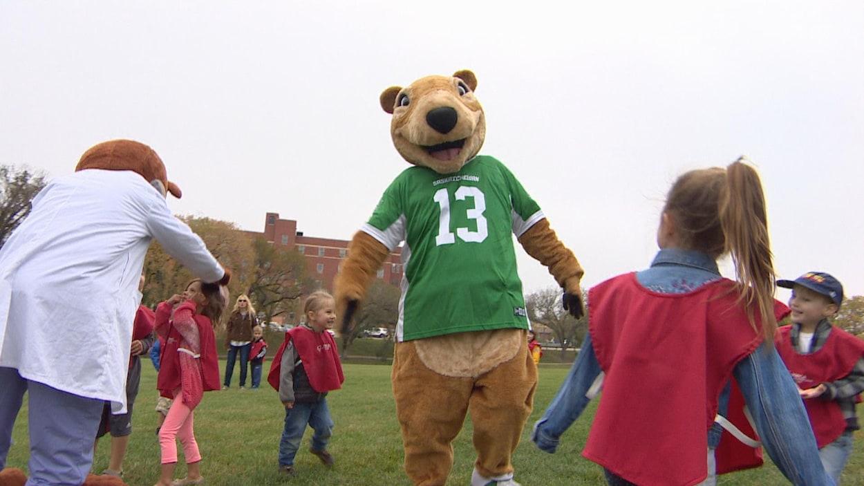 La mascotte de l'équipe des Riders, une personne avec un costume d'écureuil en peluche portant un maillot vert, joue avec des enfants sur un gazon.