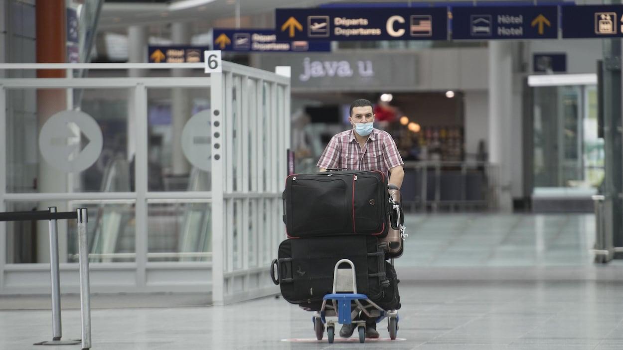 Un homme portant un masque transporte un chariot de bagages.