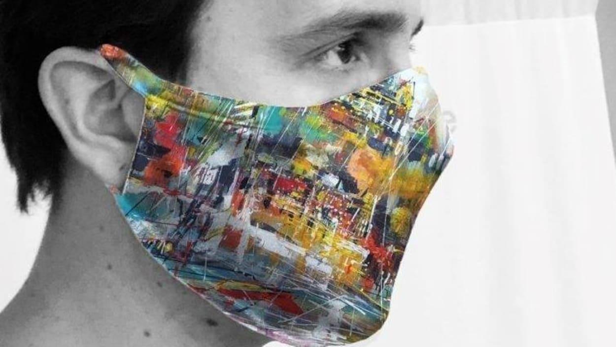 Un homme porte un masque coloré qui couvre son nez et sa bouche.