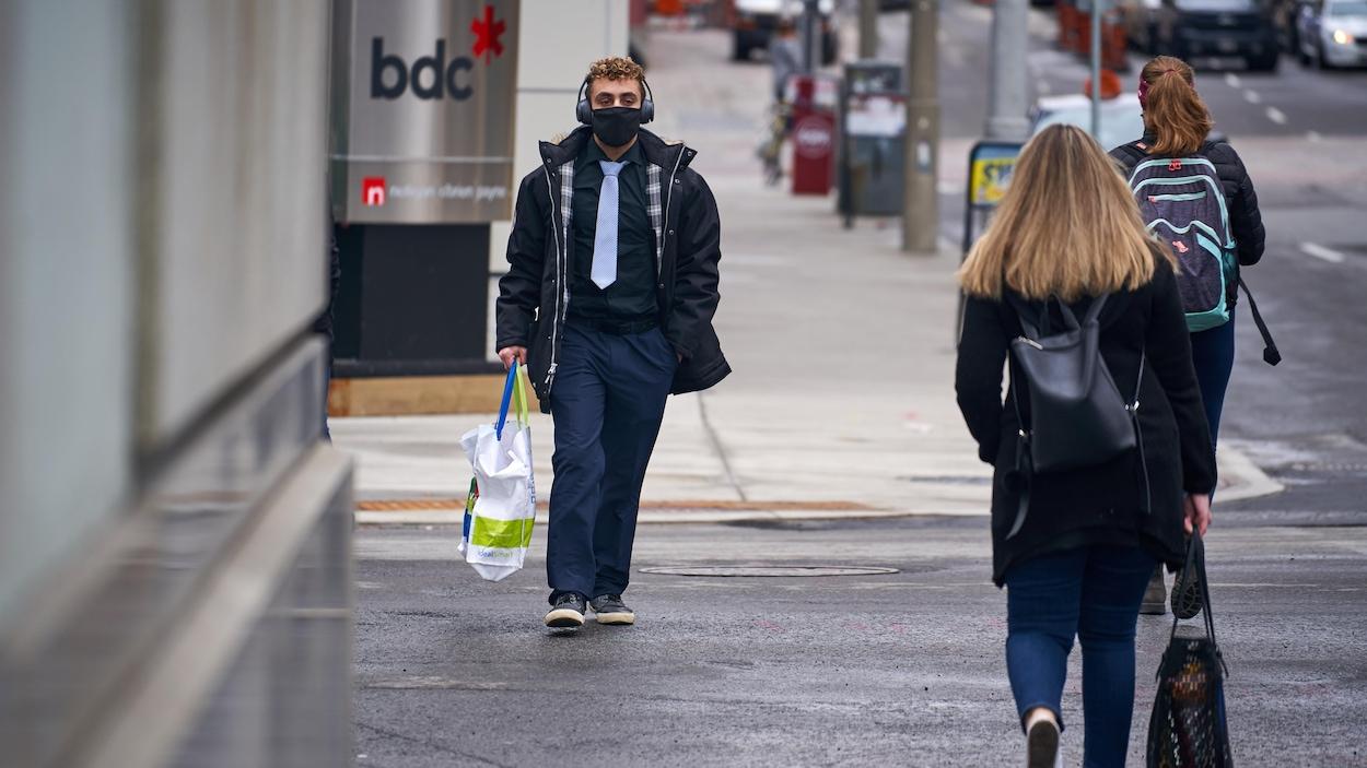 Un homme marche dans la rue avec un masque sur le visage.