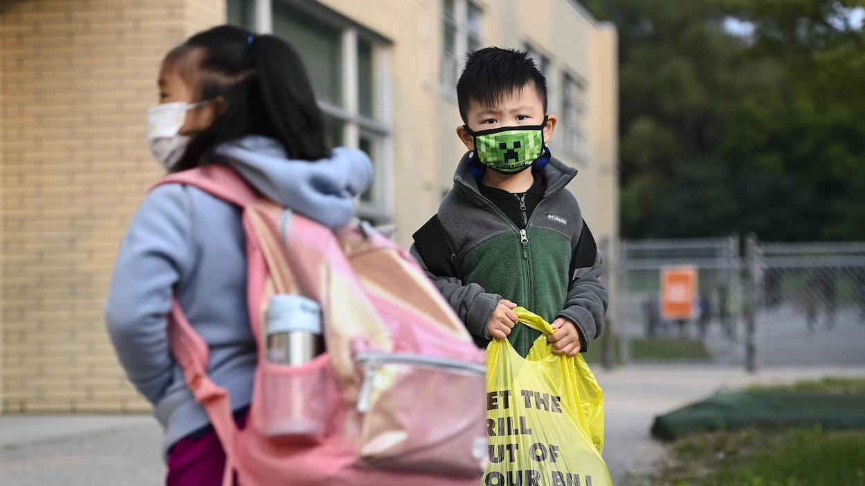 Deux élèves portent le masque à l'extérieur d'une école à Toronto.