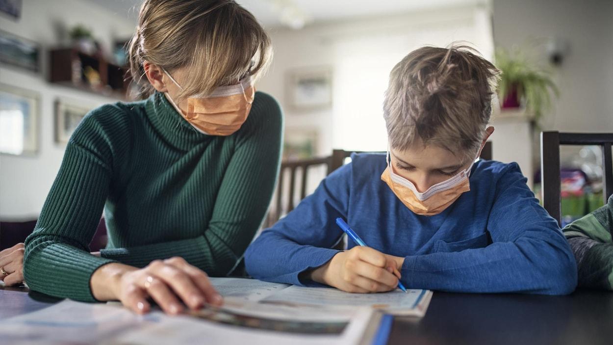 Un jeune et sa mère à la maison portent un masque.