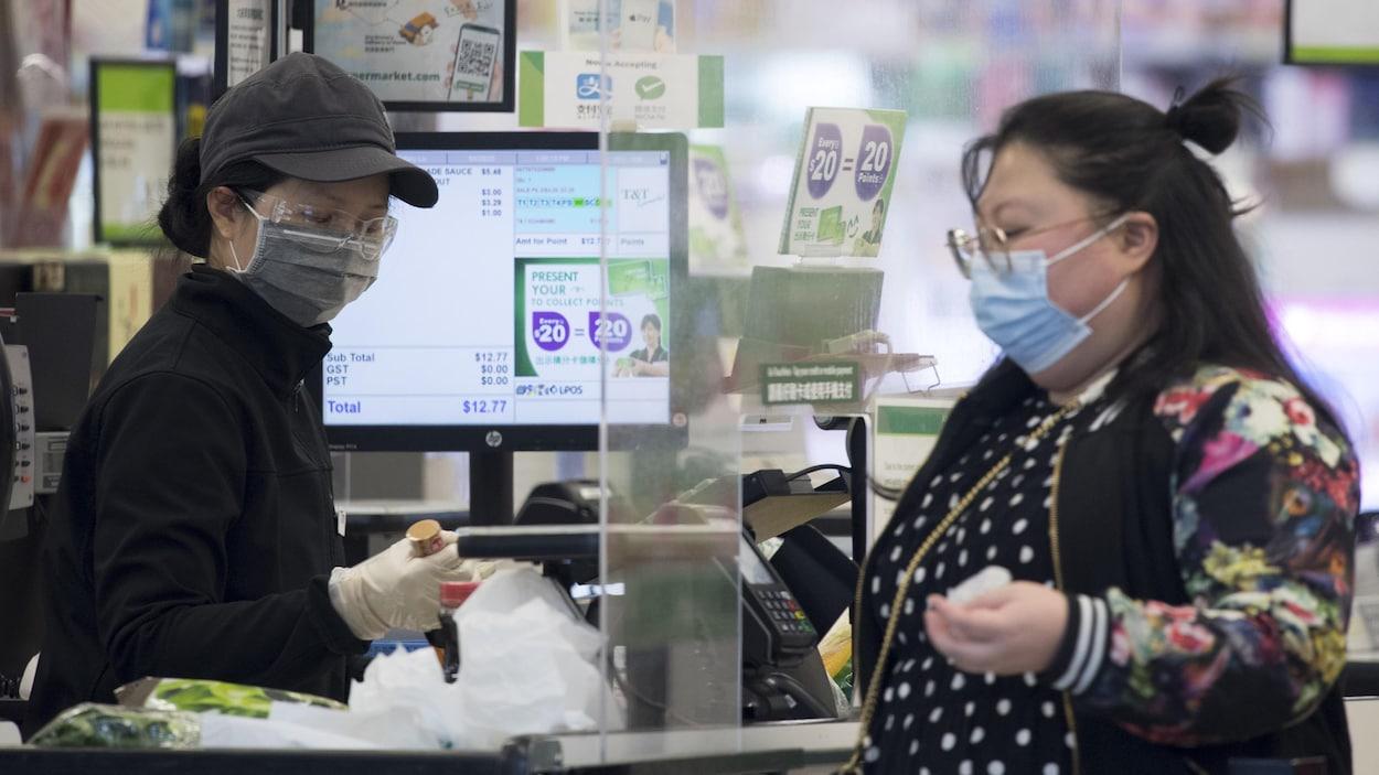 Une caissière et une cliente portent un masque à l'épicerie.
