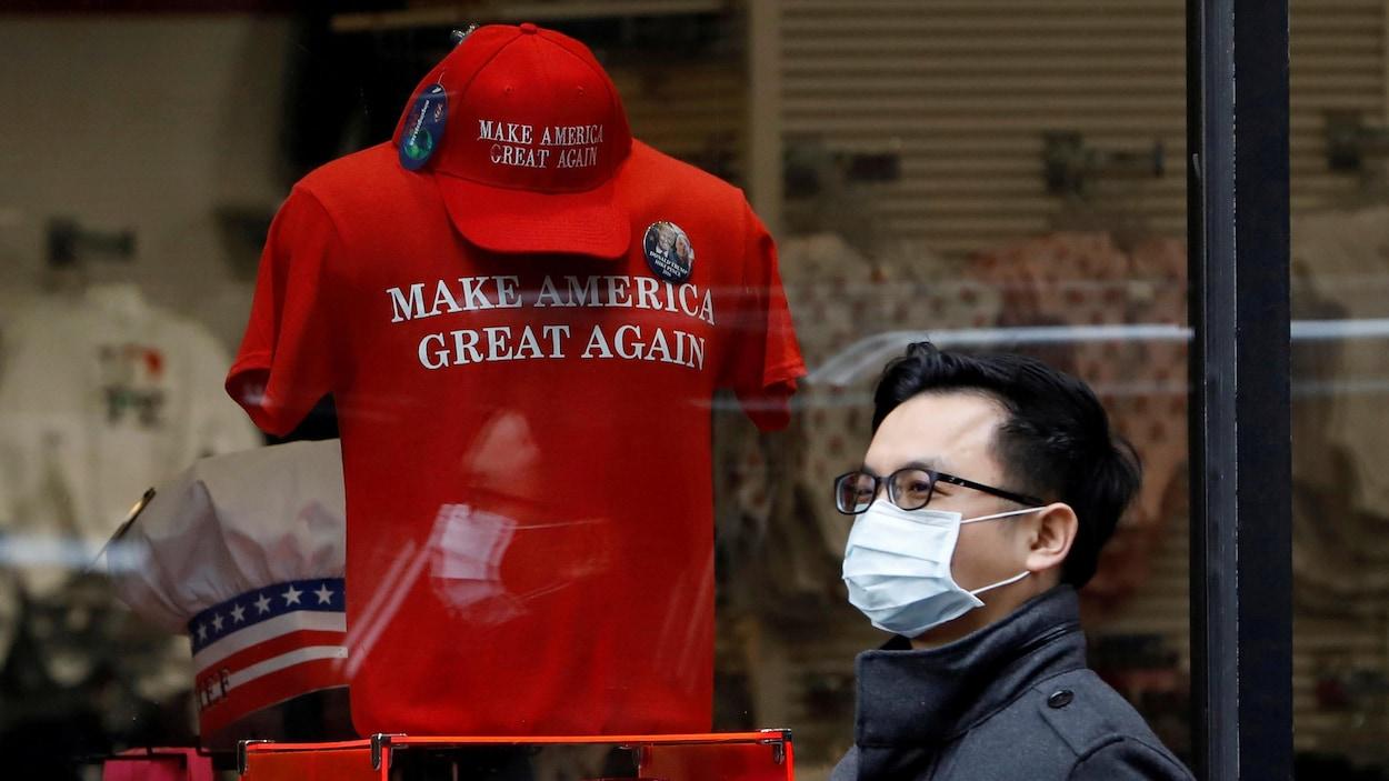Un homme portant un masque chirurgical passe devant une vitrine où l'on vend un chandail « Make America Great Again ».