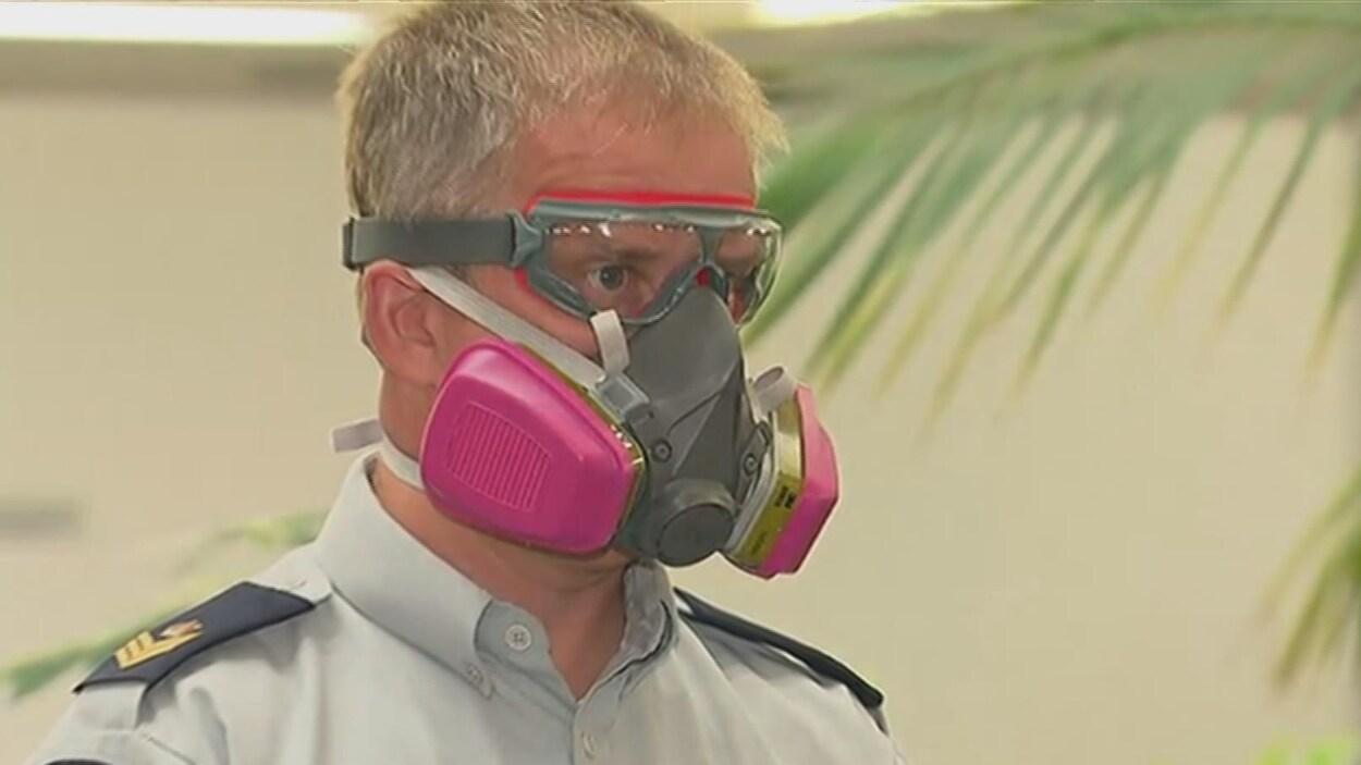 Un agent de la GRC porte un masque et des lunettes conçues pour protéger contre des substances dangereuses comme le fentanyl