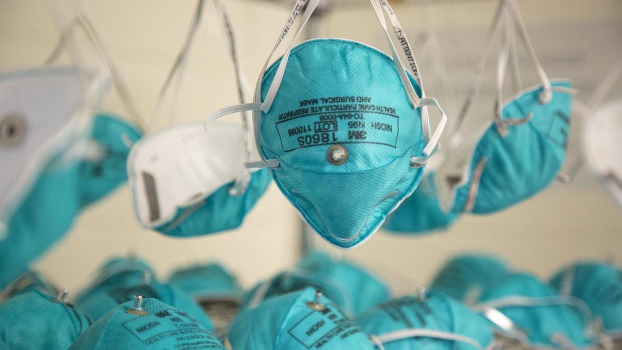 Des masques N95 sont suspendus après décontamination.