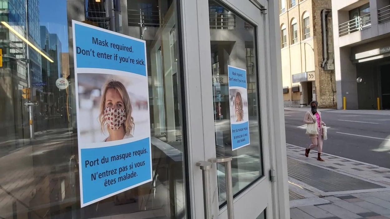 Une affiche sur la porte extérieure d'un immeuble donnant accès au train léger rappelle que le porte du masque est requis.
