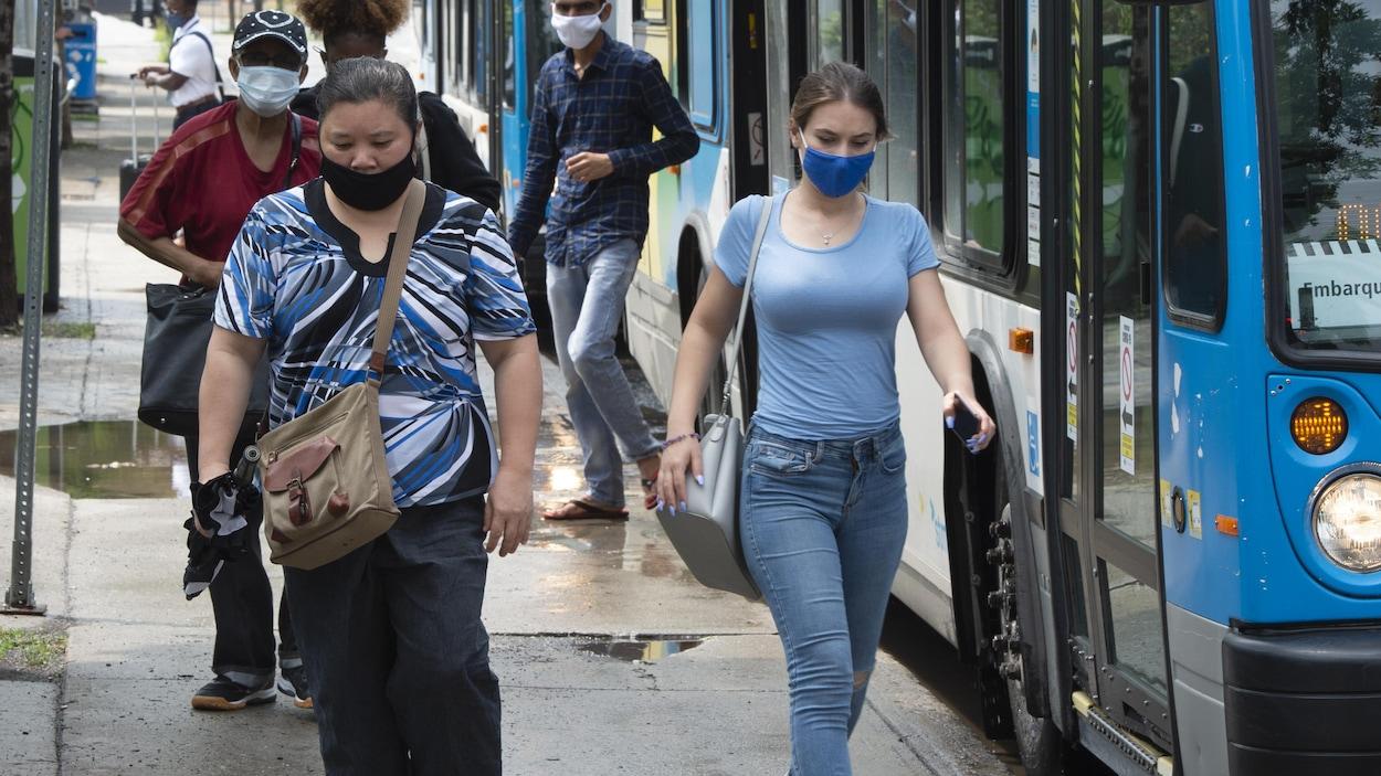 Des passagers débarquant d'un autobus à Montréal.