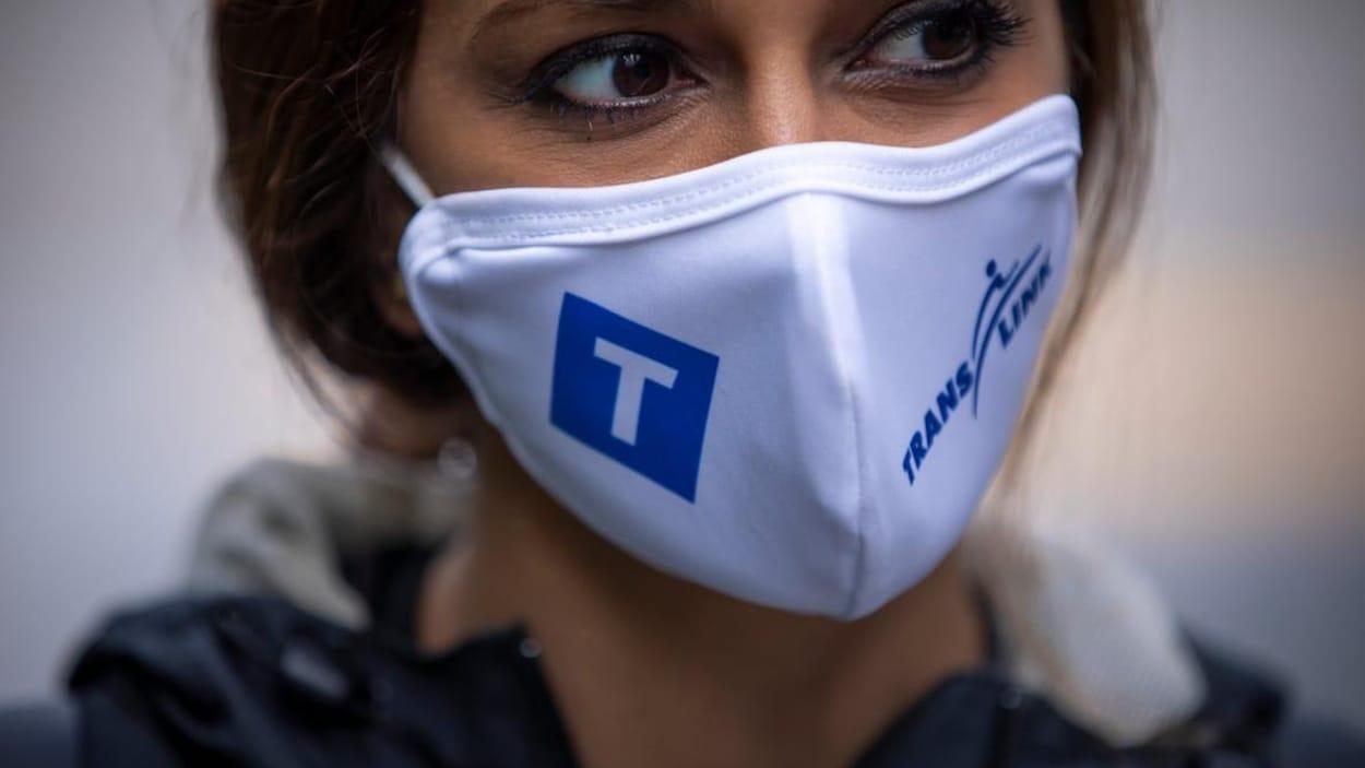 Une femme porte un masque à l'effigie de la Société des transports de Vancouver, TransLink.