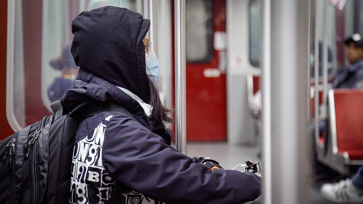 Une femme portant un masque est assise dans le métro de Toronto.
