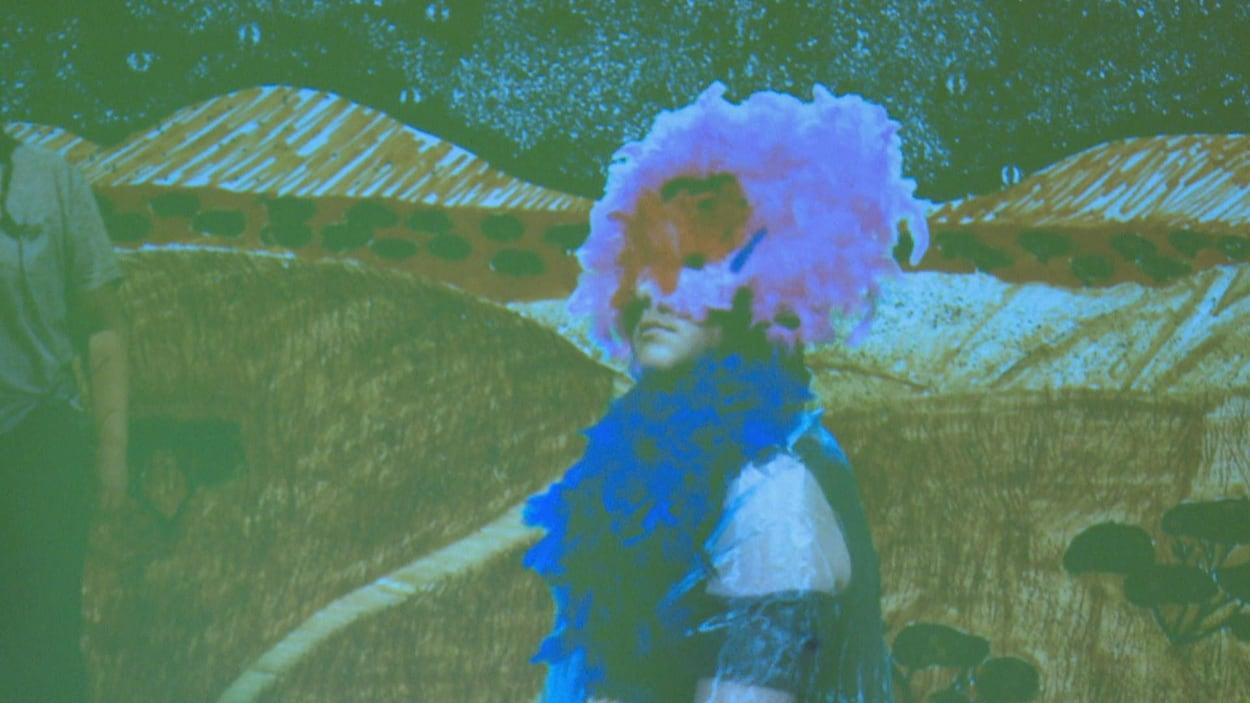 Un jeune arborant un masque à plumes roses devant un décor dessiné.
