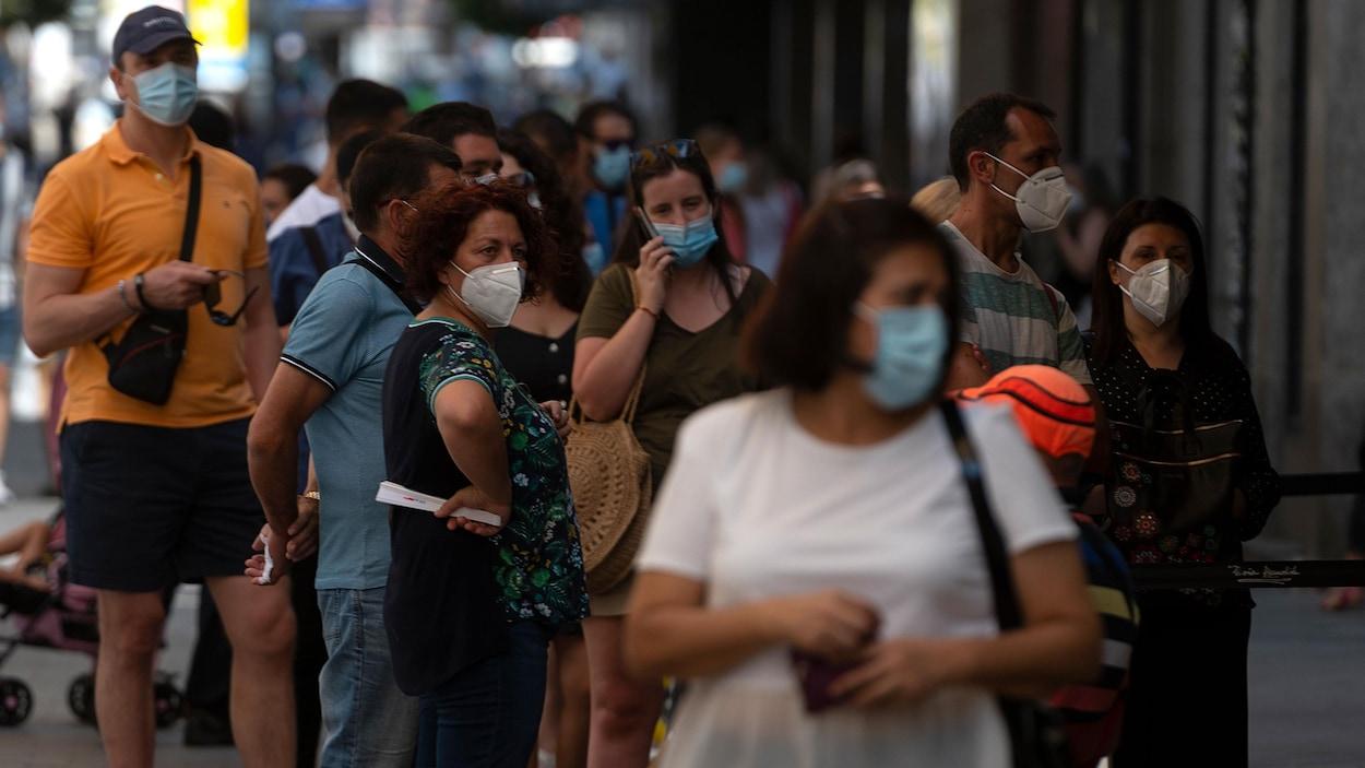Des Espagnols portant des masques dans la rue.