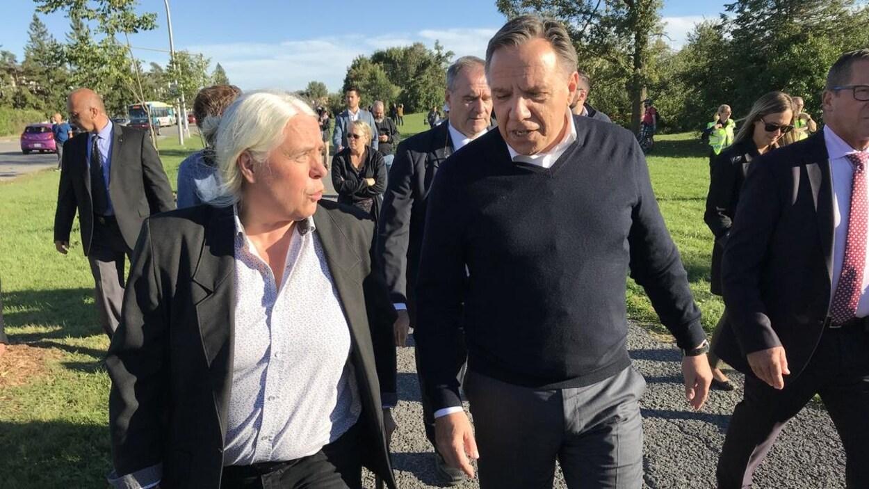 Manon Massé et François Legault discutent en marchant dans un parc de Gatineau près de bâtiments endommagés par la tornade.