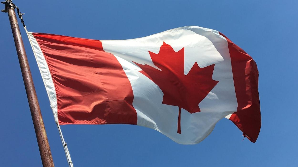 Un drapeau du Canada flottant dans le vent, attaché sur un mat.