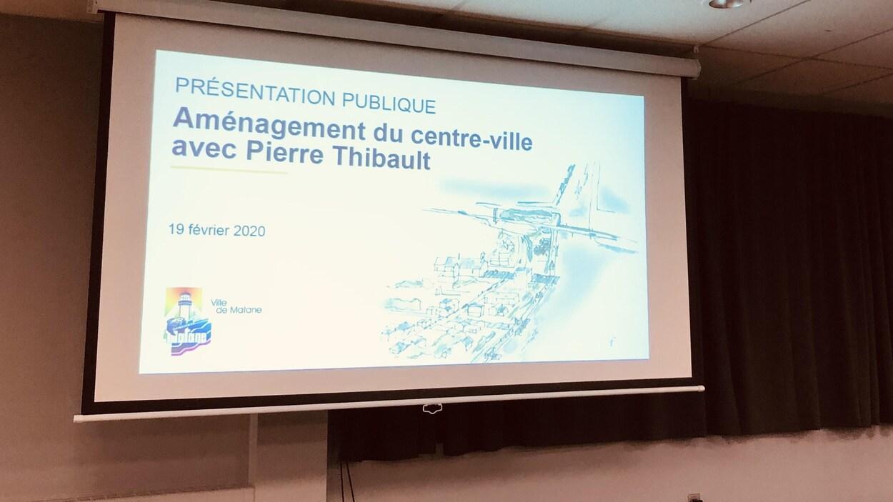 Une image projetée où on peut lire « Présentation, aménagement du centre-ville avec Pierre Thibault ».