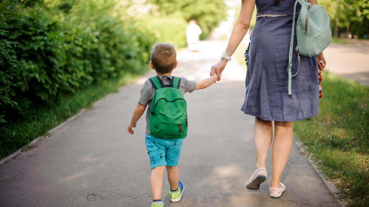 Une mère marchant dans la rue avec son fils et son sac à dos par une journée ensoleillée d'été.