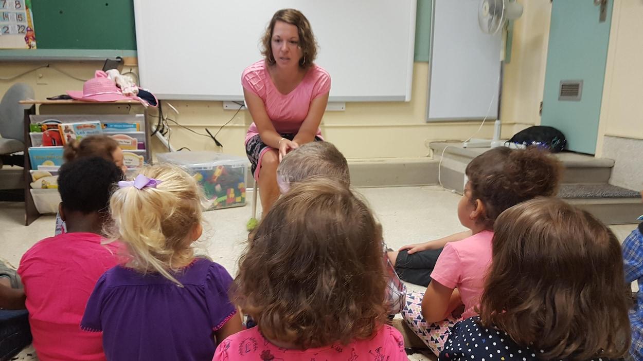 Une enseignante discute avec des enfants dans une classe de maternelle.