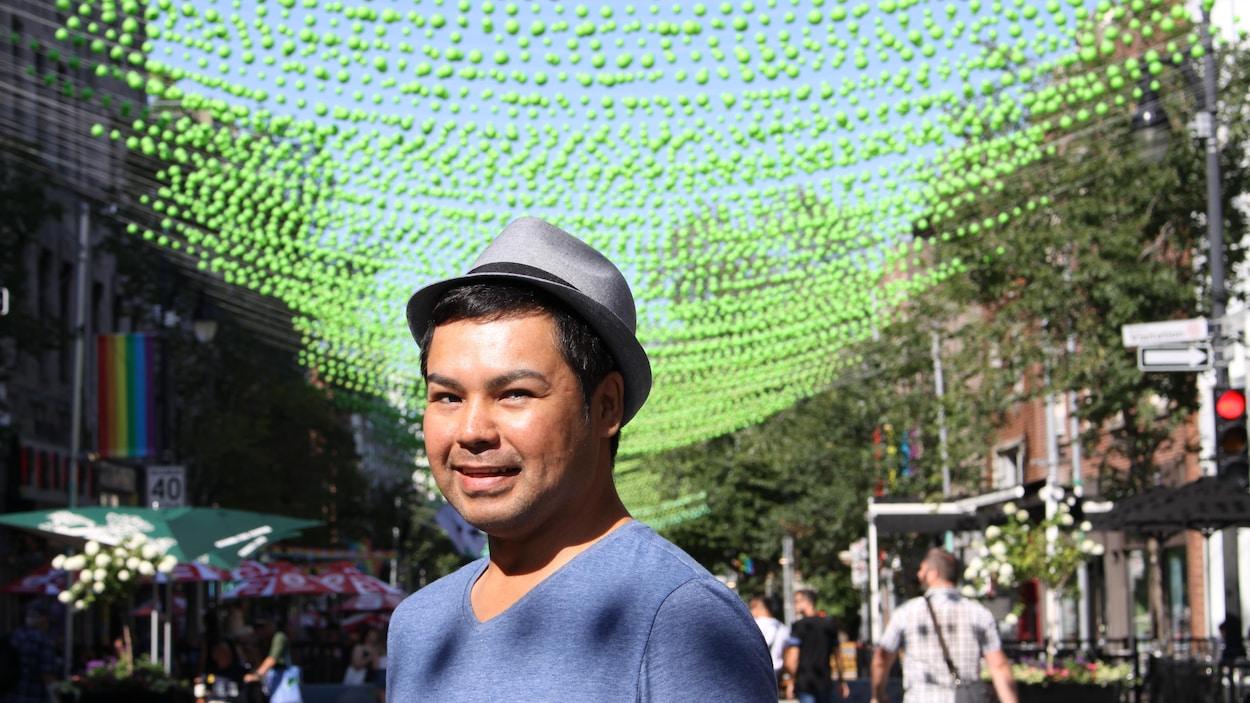 L'homme sourit à la caméra et derrière lui on voit les boules vertes qui surplombent la rue Sainte-Catherine dans le village gay.
