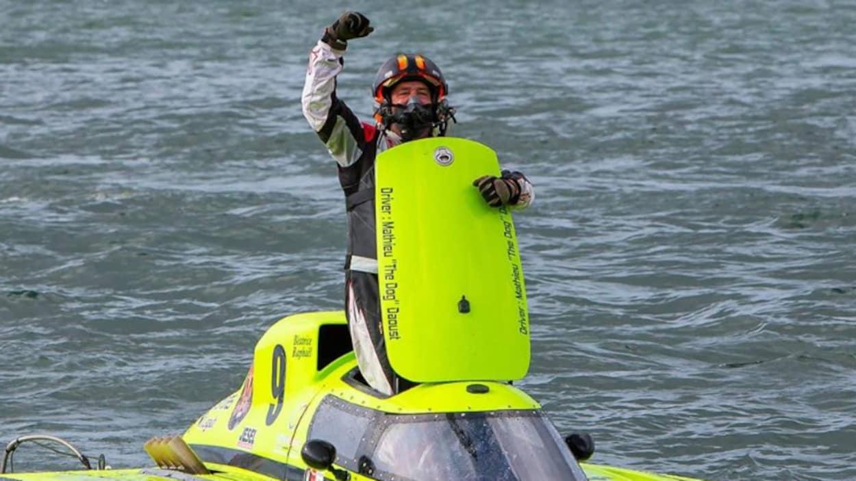 Un homme fait un signe de victoire dans une embarcation