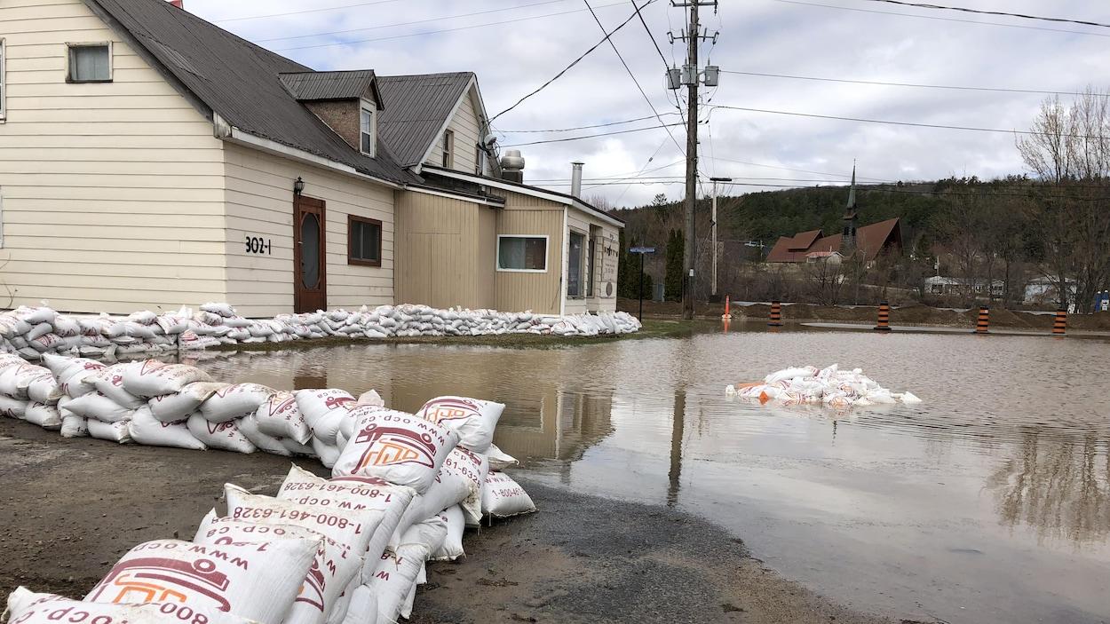 Des sac de sable protège une maison de l'eau qui déborde de la rivière.
