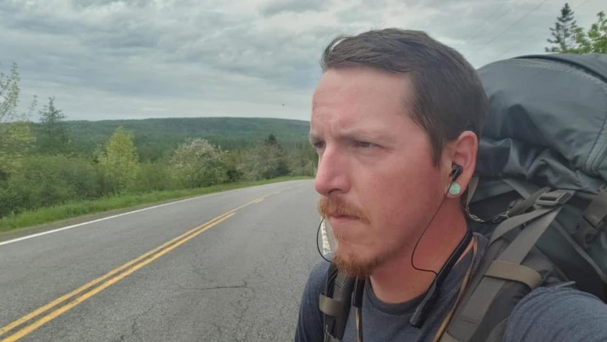 Un homme de profil avec des écouteurs et un sac à dos, en bord de route