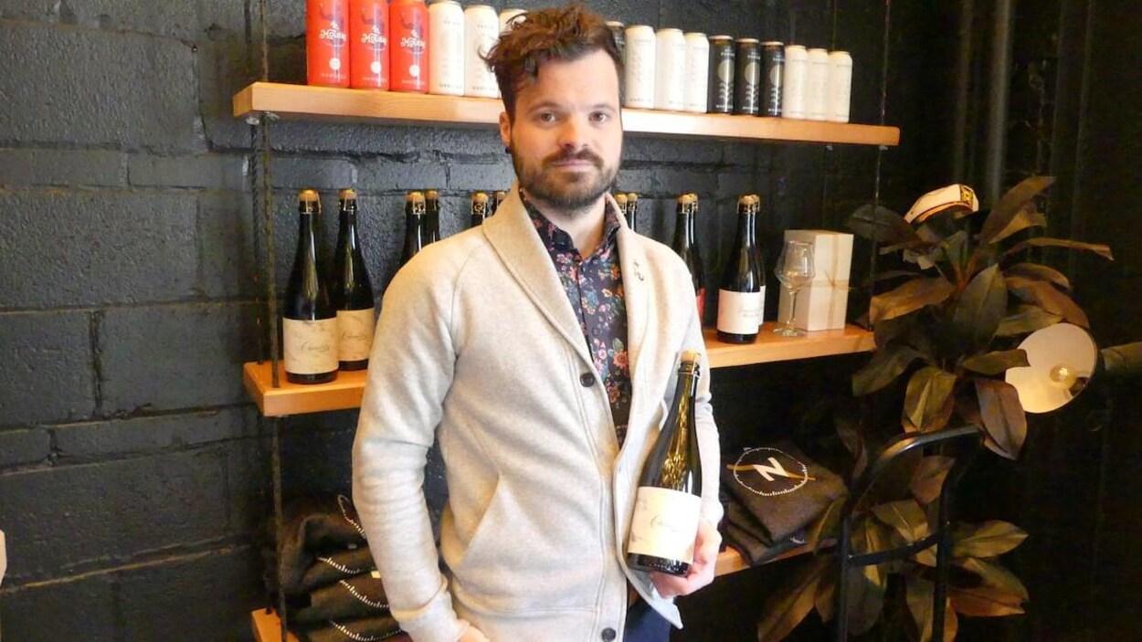 Le président et copropriétaire de la brasserie NonSuch, Matthew Sabourin, tenant une bouteille de sa production.