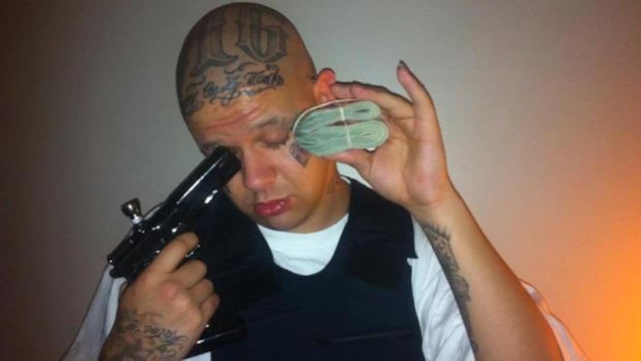 Un homme blanc avec pleins de tatouages dans le visage, pointant une fausse arme convertie en bong de marijuana vers sa figure. Il tient aussi une liasse d'argent