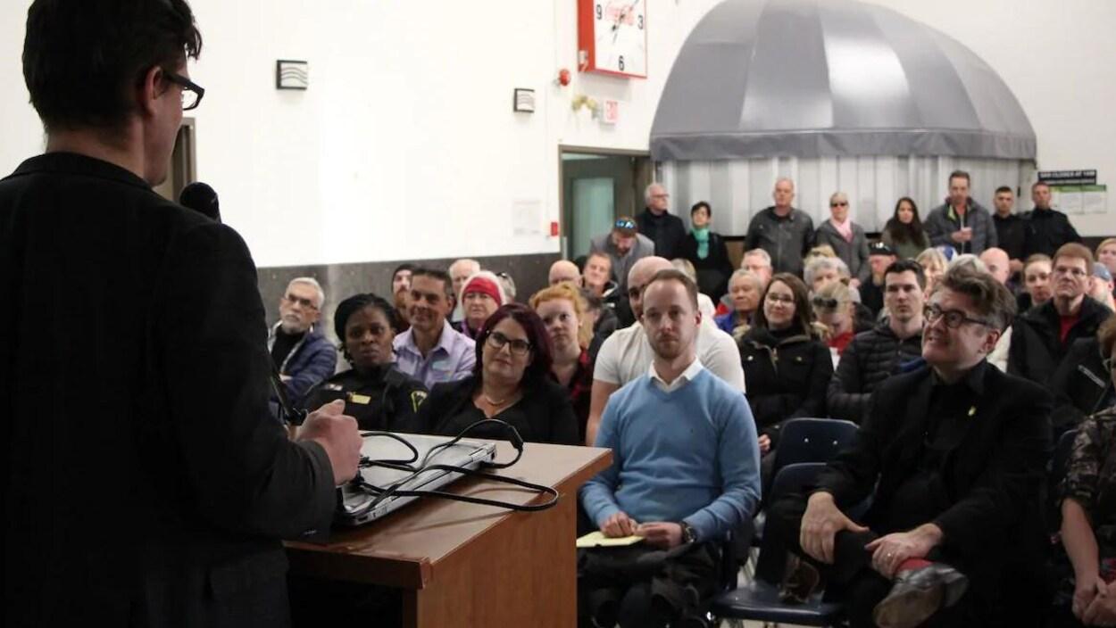 Un homme s'adresse à une foule de gens assis.