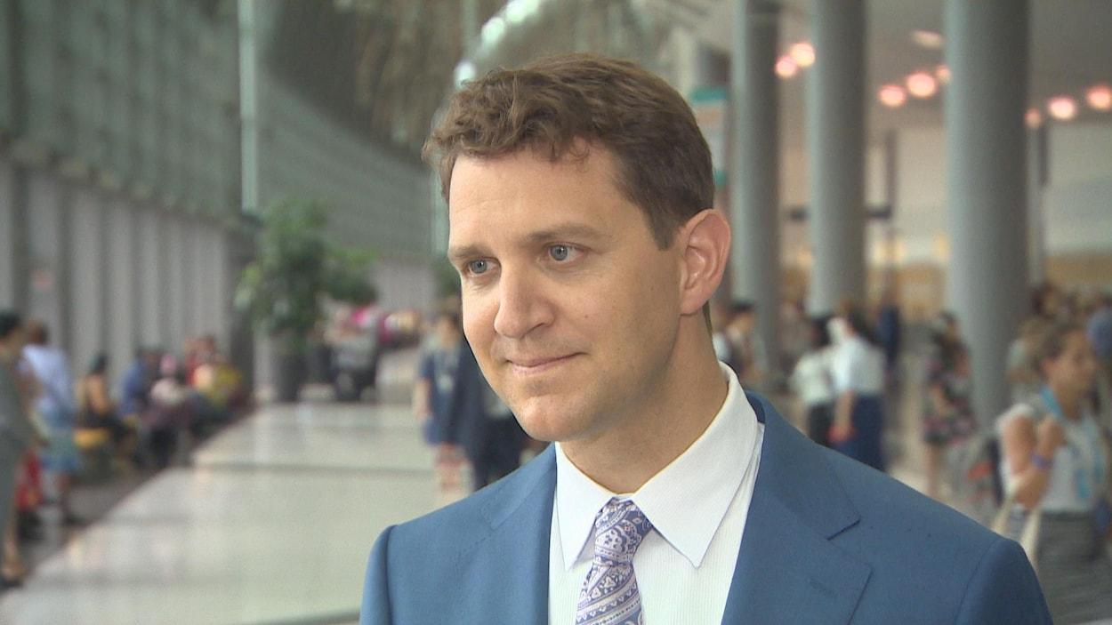 Le porte-parole national des Témoins de Jéhovah, Matthieu Rozon, porte un veston bleu et une cravate violette à motifs; il a les yeux bleus et les cheveux châteaux courts.