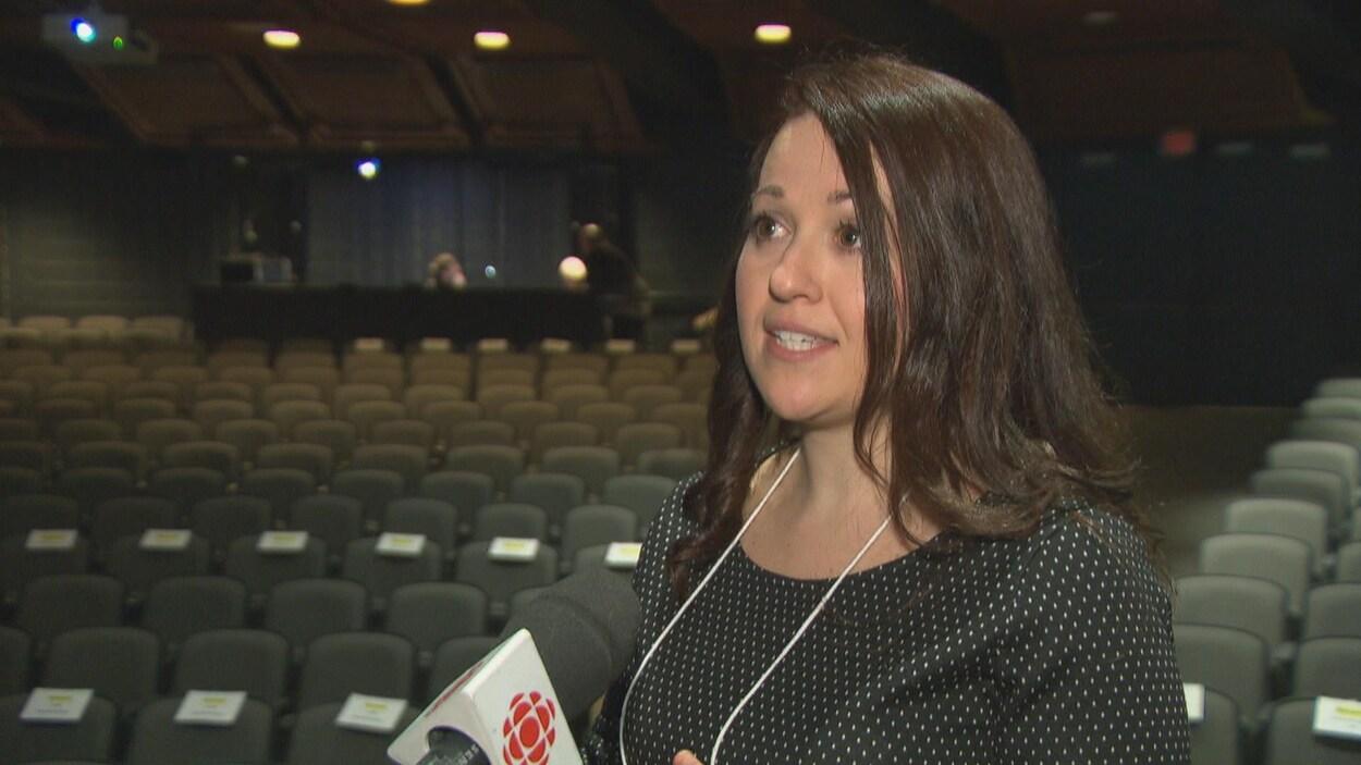 Une femme en entrevue dans une salle de spectacle
