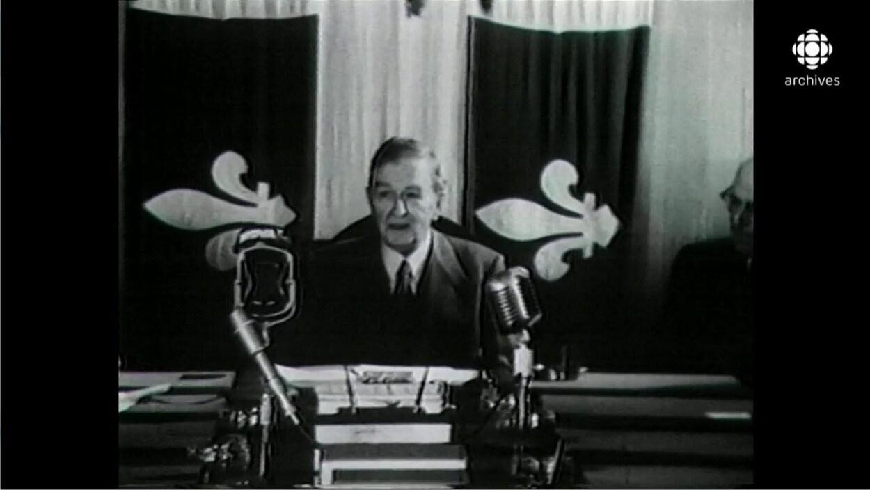 Image en noir et plan de Maurice Duplessis, assis à un bureau massif équipé de micros, avec en arrière-plan un grand drapeau du Québec