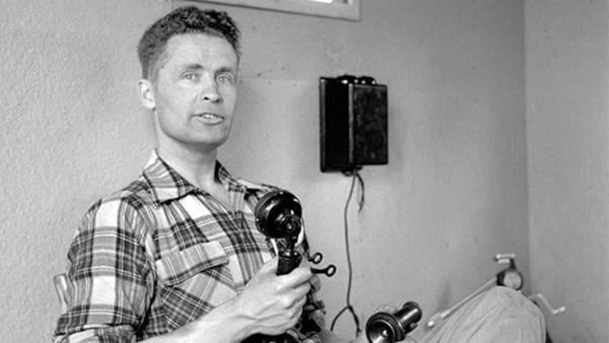 Max Ward, assis contre un mur, tient un vieux téléphone.